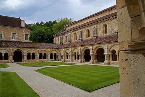 フォントネー修道院 中庭を十字に走る道と外の林も入れた回廊写真