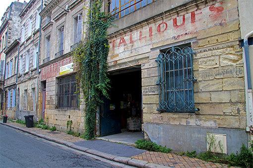 ボルドー ポムドール通りの建物1Fの壁と書かれた赤文字のかすれた商号