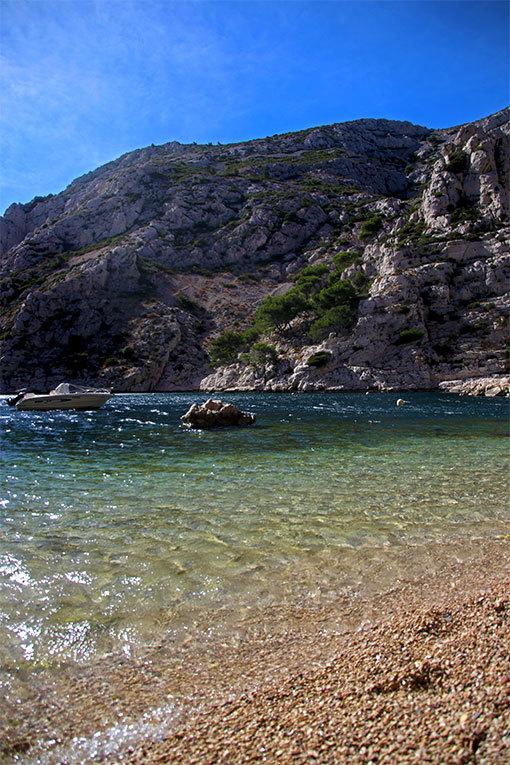モルジウカランクの小ビーチ 縦向き写真 砂と透明な水と向こうの岩と